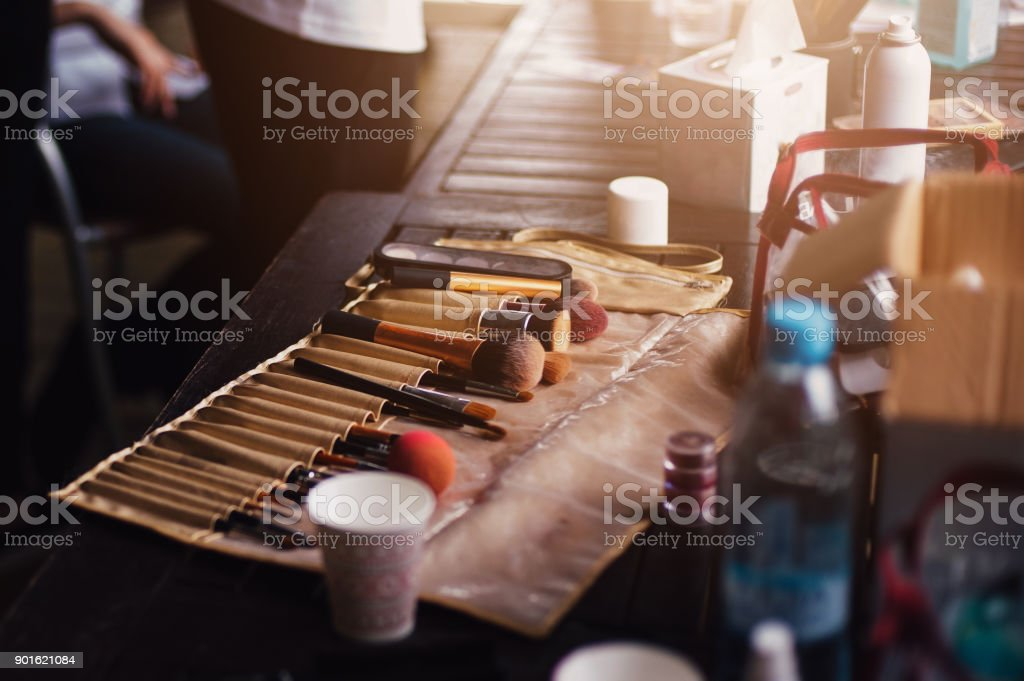 Table make-up artist at the backstage - brushes, cosmetics, sponges,...