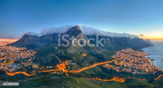 Table Mountain covered by its typical cloud table cloth and the twelve Apostles. Below on the left you can see Cape Town and the beautiful Camps Bay on the right. Taken right after sunset.