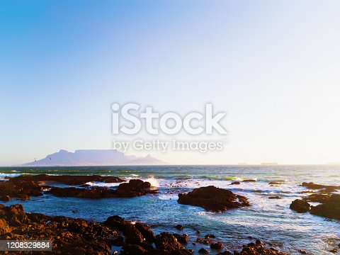 Looking from a rocky shore at Bloubergstrand across Table Bay to the iconic Table Mountain at the foot of South Africa. In the far distance are two silhouetted kite surfers.