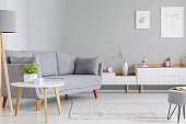 Table next to grey sofa in scandi living room interior with posters above cupboard. Real photo