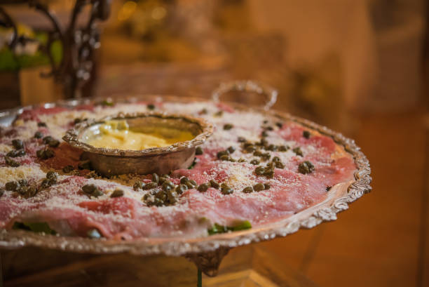 table of cold cuts, carpaccio with capers and grated Parmesan cheese table of cold cuts, carpaccio with capers and grated Parmesan cheese reveillon stock pictures, royalty-free photos & images