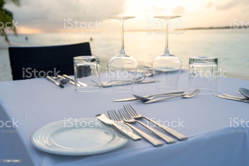 Der Tisch im Freien neben dem Meer bietet eine besondere romantische Mahlzeit an. – Foto