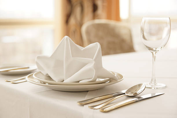 A table place setting with a golden napkin stock photo