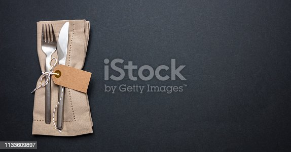 Business lunch, Table place setting with linen napkin and blank tag on black color background, banner, top view, copy space