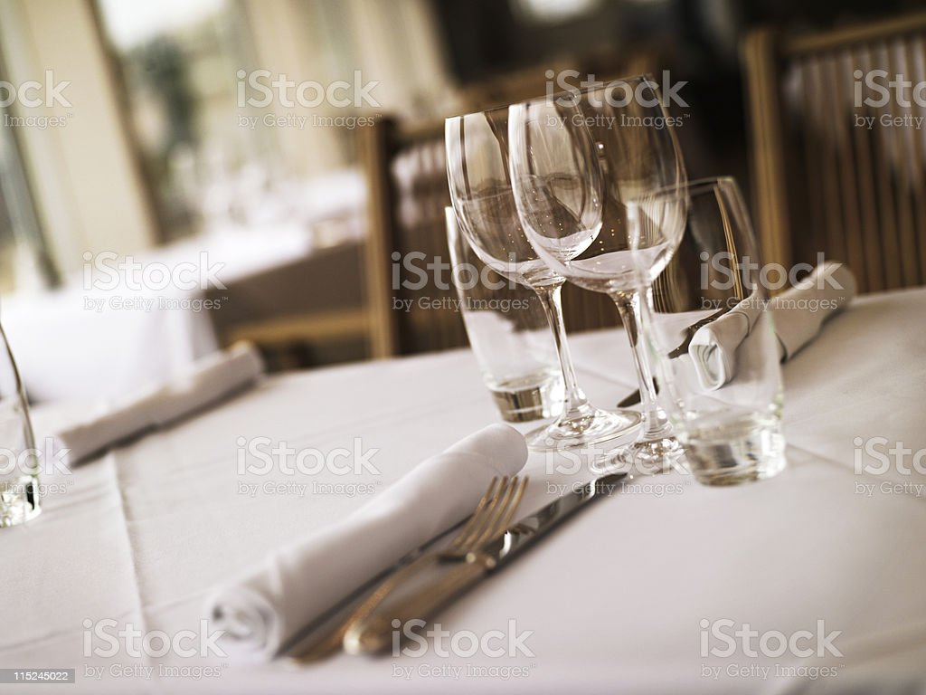 Table place settings with white tablecloth at restaurant royalty-free stock photo