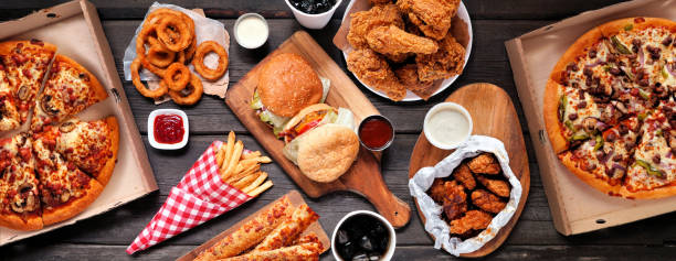 Table scene of assorted take out or delivery foods, top down view on a dark wood banner stock photo