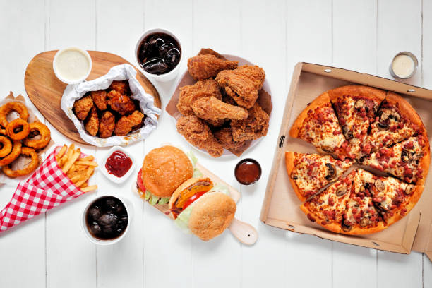 Table scene with large variety of take out and fast foods, top view over white wood stock photo