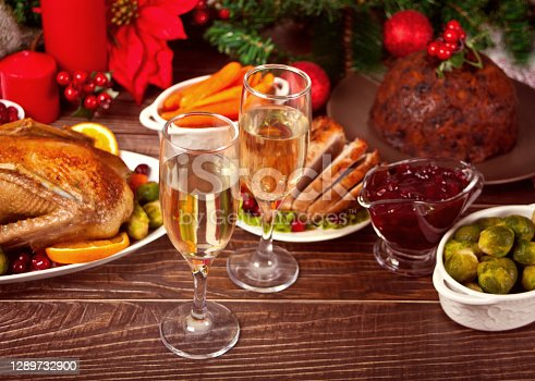 Table served for thanksgiving or Christmas dinner. Two glasses of wine or champagne. Stuffed roasted turkey in the foreground. Traditional celebrating holiday. Top view.