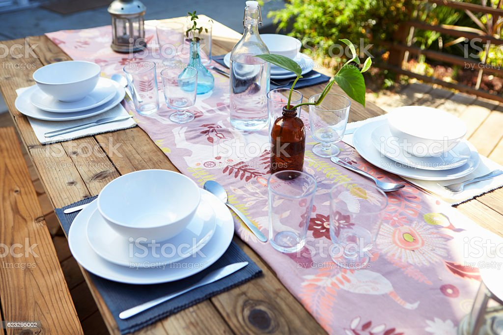 Table Set For Outdoor Meal On Wooden Table In Garden stock photo