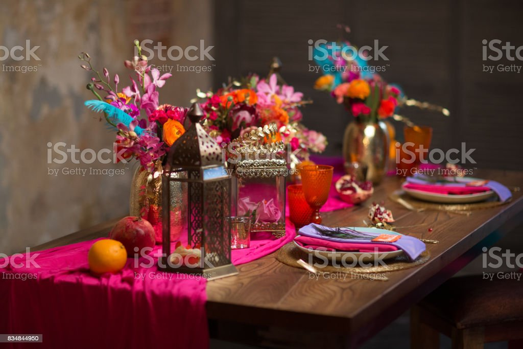 A Table Set Vase With Flowers Plates Decorate In Purple And Pink