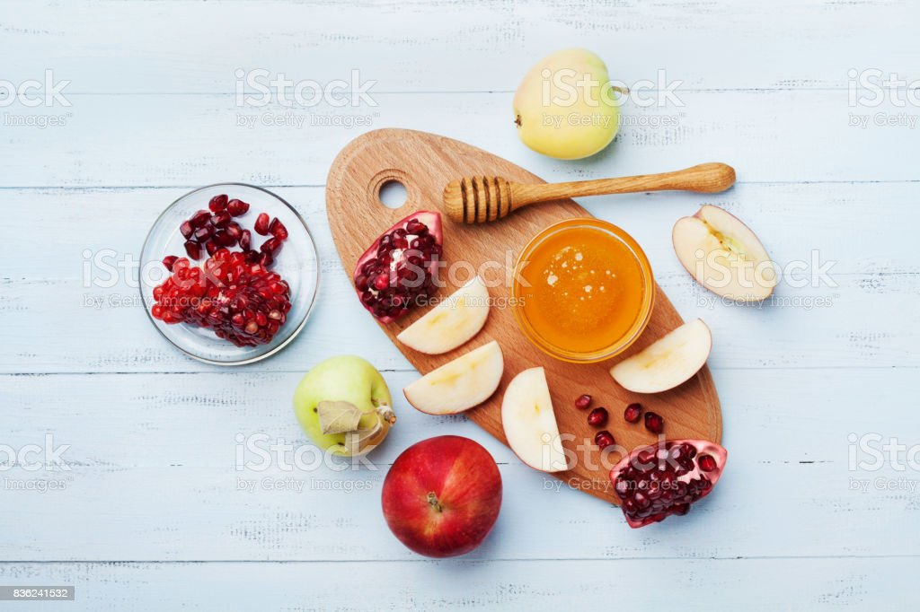 Table set with traditional food for Jewish New Year Holiday, Rosh Hashana. Honey, apple slices and pomegranate. Flat lay. stock photo