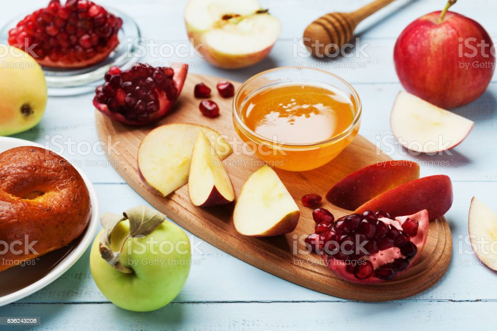 Table set with traditional food for Jewish New Year Holiday, Rosh Hashana. Honey, apple slices, pomegranate and hala. stock photo