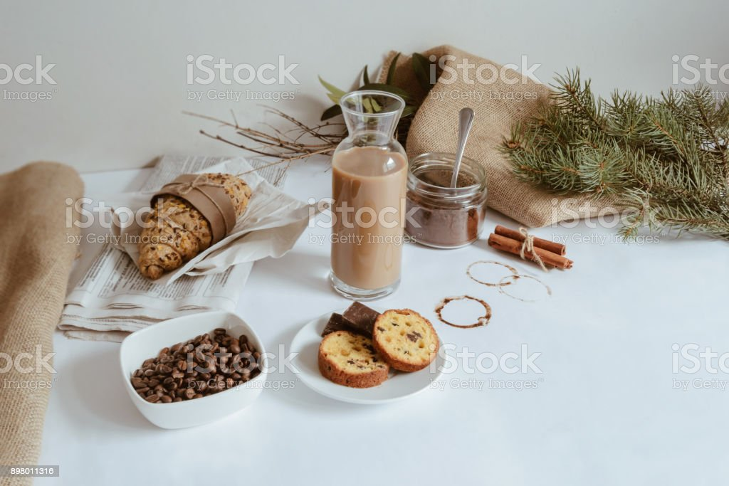 A table setting consisting of a croissant, chocolate milk, coffee beans, coffee and a biscuits stock photo