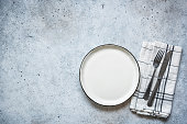 Table setting empty plate and cutlery on concrete background. Table top view. Top view