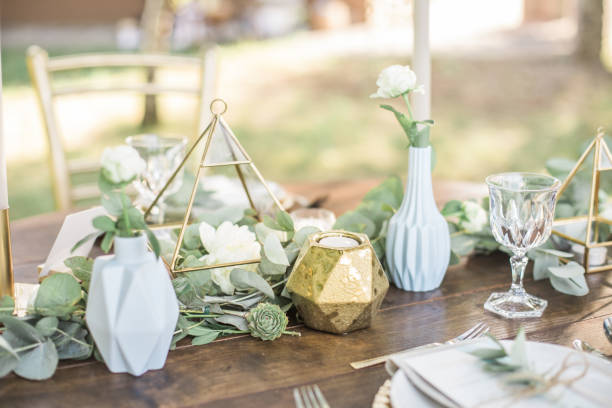 table setting for an event party or wedding reception, decorated with geometric shape vases, gold candles eucalyptus branches and flowers. - home decor boho imagens e fotografias de stock