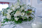 fancy wedding decoration on the table with flower arangments, drinking glasses and candles. pastel colors.