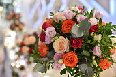 Table setting for an wedding reception. flower arangment in close up view. Combination of orange,yellow and pink roses.