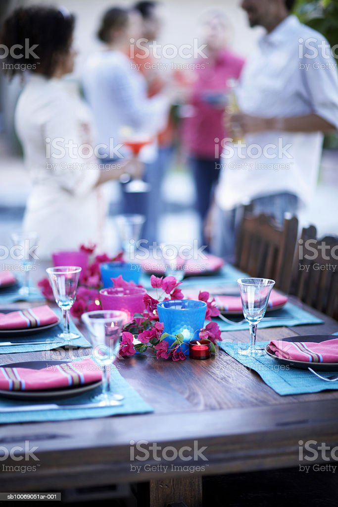 Table setting for dinner party, people standing in background royalty-free stock photo