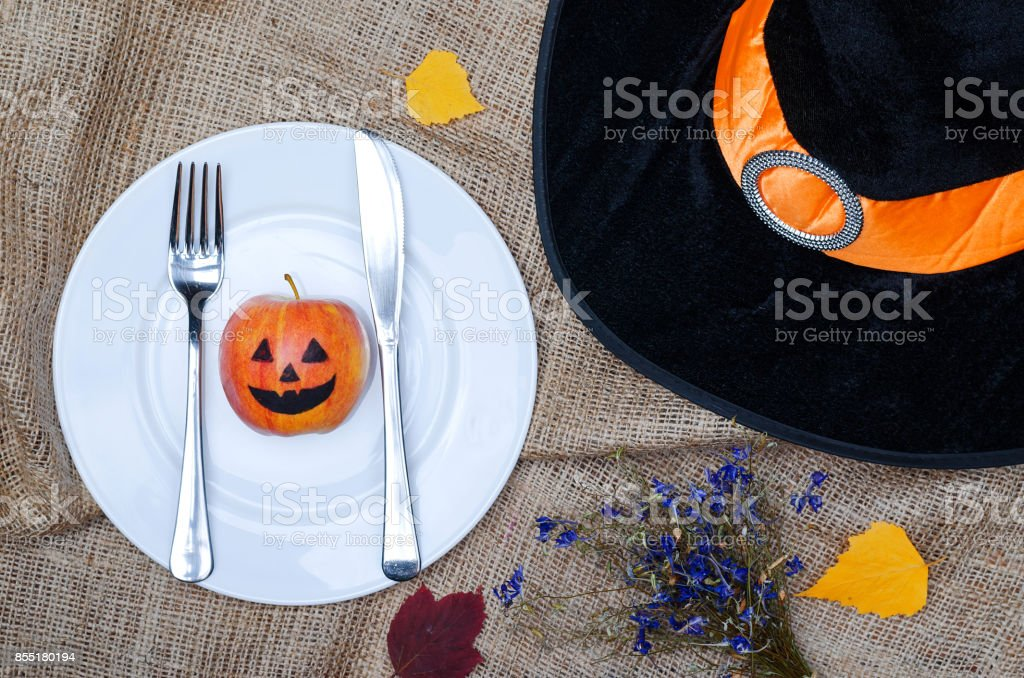 Table setting for halloween: plate, hat of a witch, leaves, top view with copy space. stock photo