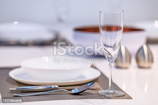 Table setting in a modern dining room with a white table and flatware, Scandinavian style