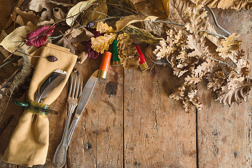 Table setting in hunting style. Vintage fork and knife, napkin with ring, duck feather, sockets and dry oak leaves on old wooden background. Space for text