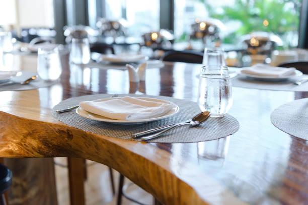 Tischlage im Restaurant. Dekoriert eleganter Tisch, Porzellanteller, Gläser, Serviette, Messer, Gabel und Löffel auf Holztisch – Foto