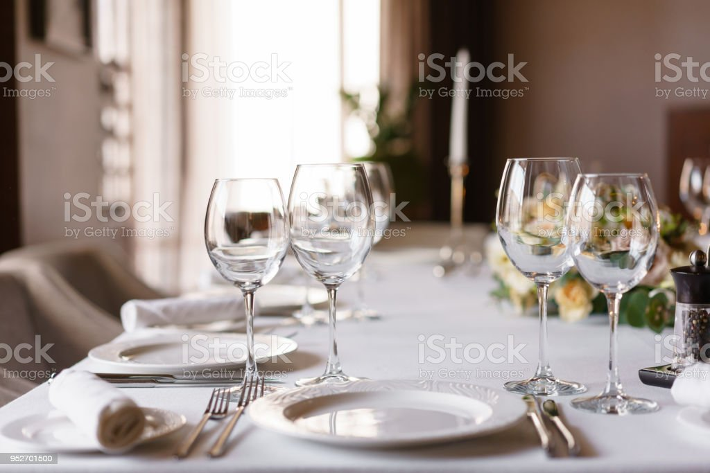 Table Setting In The Restaurant, Glasses In The Foreground. Luxury Wedding  Reception. Flower