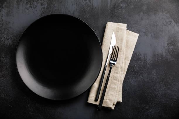 tischeinstellung mit leerer schwarzer platte, gabel und messerbesteck und leinenserviette auf dunklem tisch - tafelbesteck stock-fotos und bilder