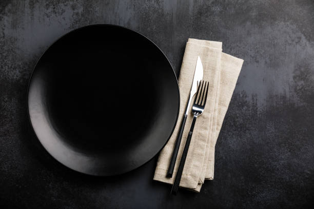 table setting with empty black plate, fork and knife cutlery and linen napkin on dark table - silverware stock pictures, royalty-free photos & images