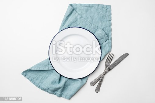 Table setting with empty plate, cutlery and linen textile isolated on white background, top view with copy space for text