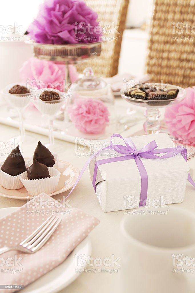 Table setting with gift box, chocolates and pink pom pons royalty-free stock photo