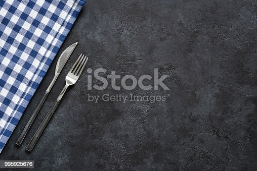 Table setting with silverware and textile on black concrete Modern cutlery, fork and knife. Restaurant silverware. Top view with copy space for text