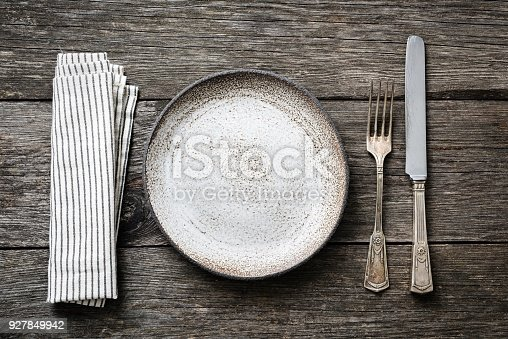 istock Table setting with vintage silverware, empty plate and napkin 927849942
