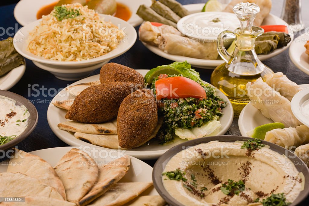 A table spread of middle-eastern dishes like hummus and pita stock photo