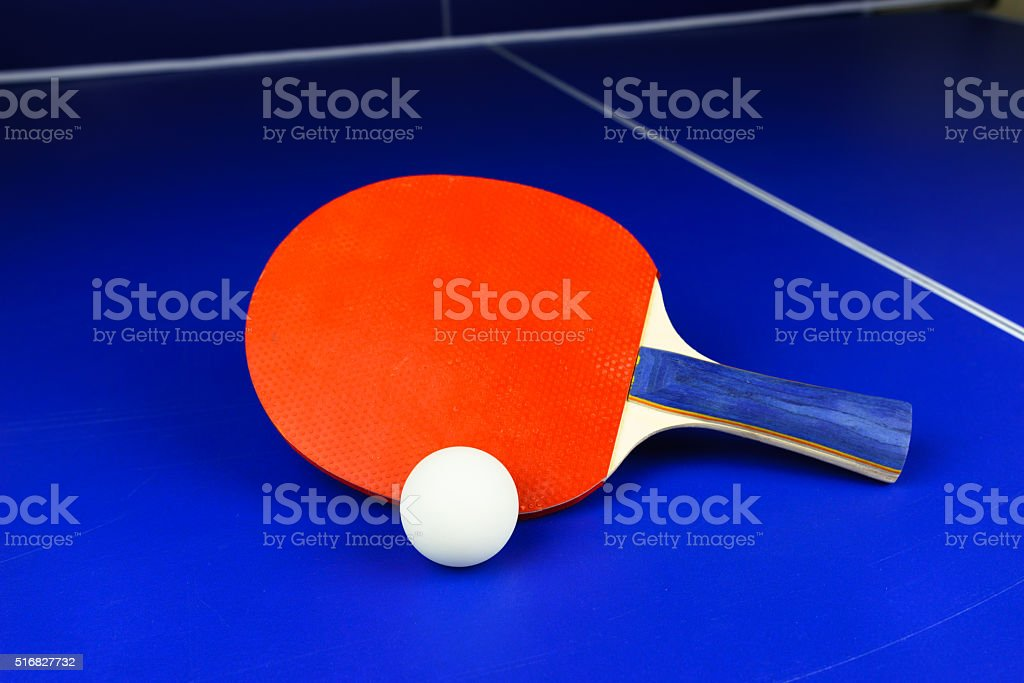 White Table Tennis Ball and a Red Racket on a Blue Table with White...