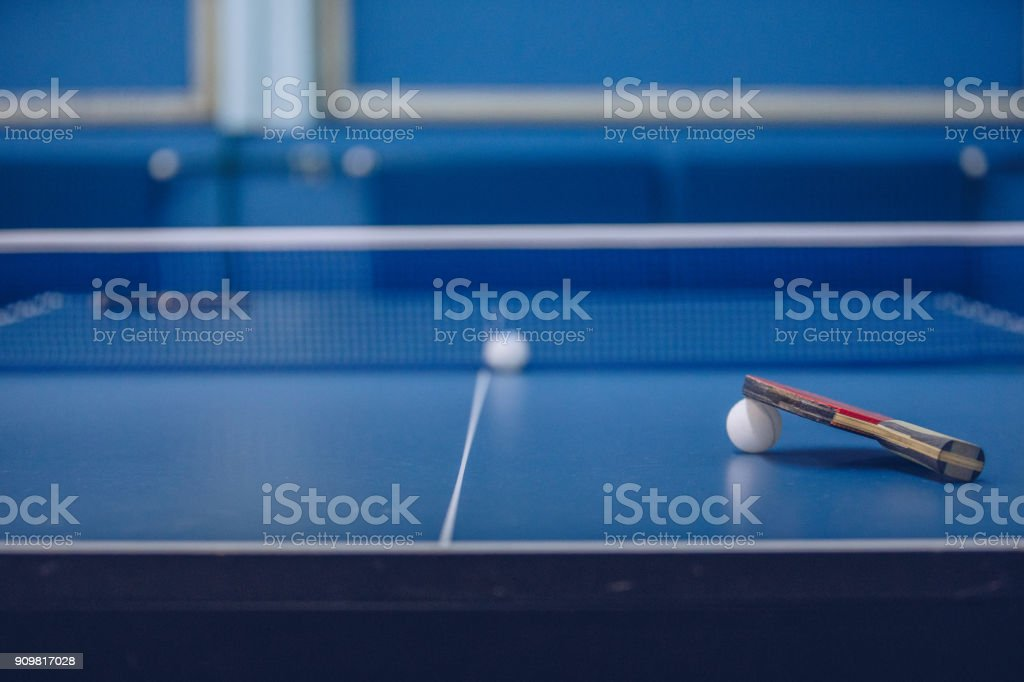 Ping pong rackets and ball on a blue ping pong table