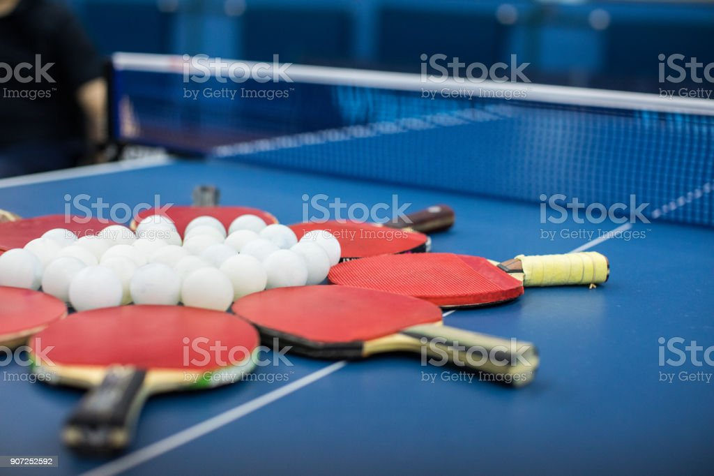 Group of Table Tennis Balls and red Bats on a blue table tennis table