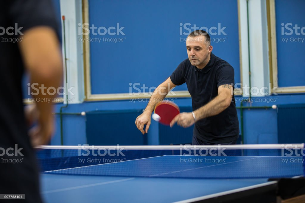 Two mature men playing table tennis indoors