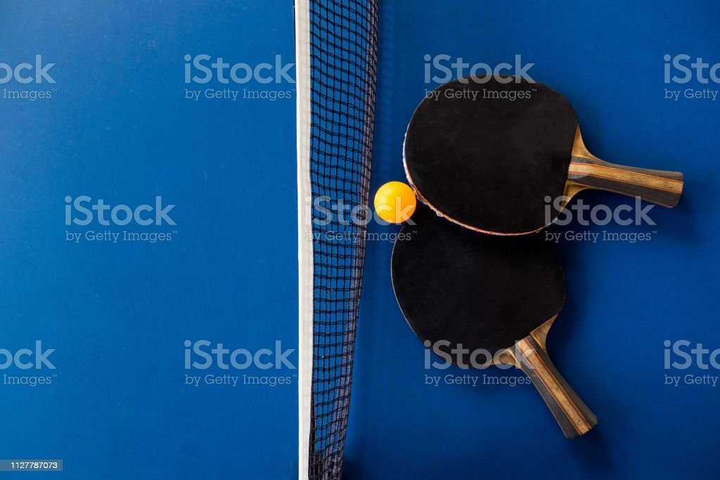 table tennis racket and ball on blue background.
