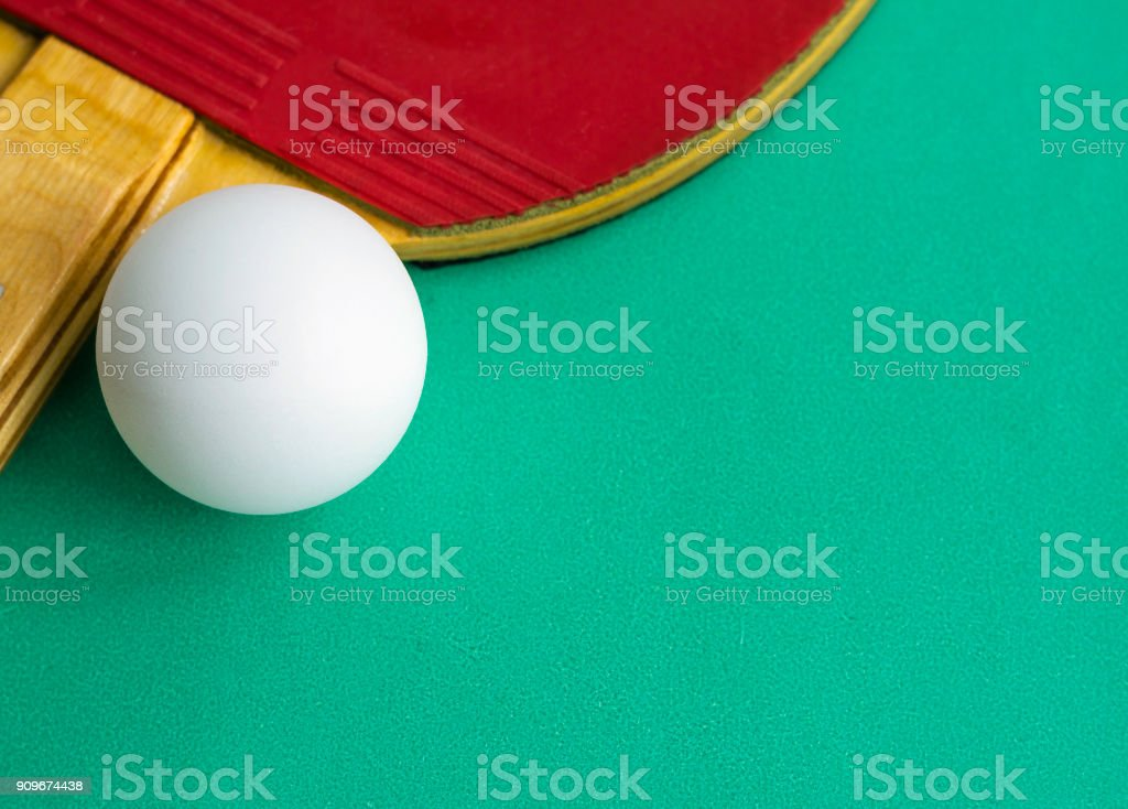 Table tennis racket with a ball on green background. Ping-pong. Image...