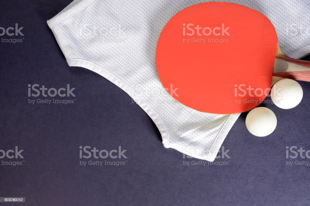 Ping pong. Table tennis rackets, balls and sports shirt on a dark...