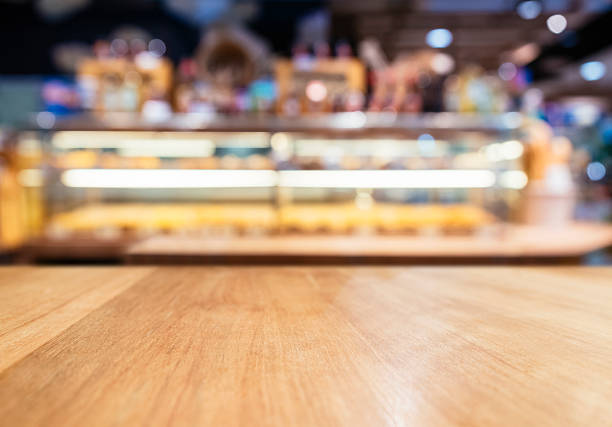 table top counter with blurred bakery display shelf - bakery stockfoto's en -beelden
