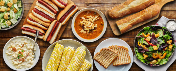 table top meal with hot dogs, grilled cheese, soup and salad stock photo