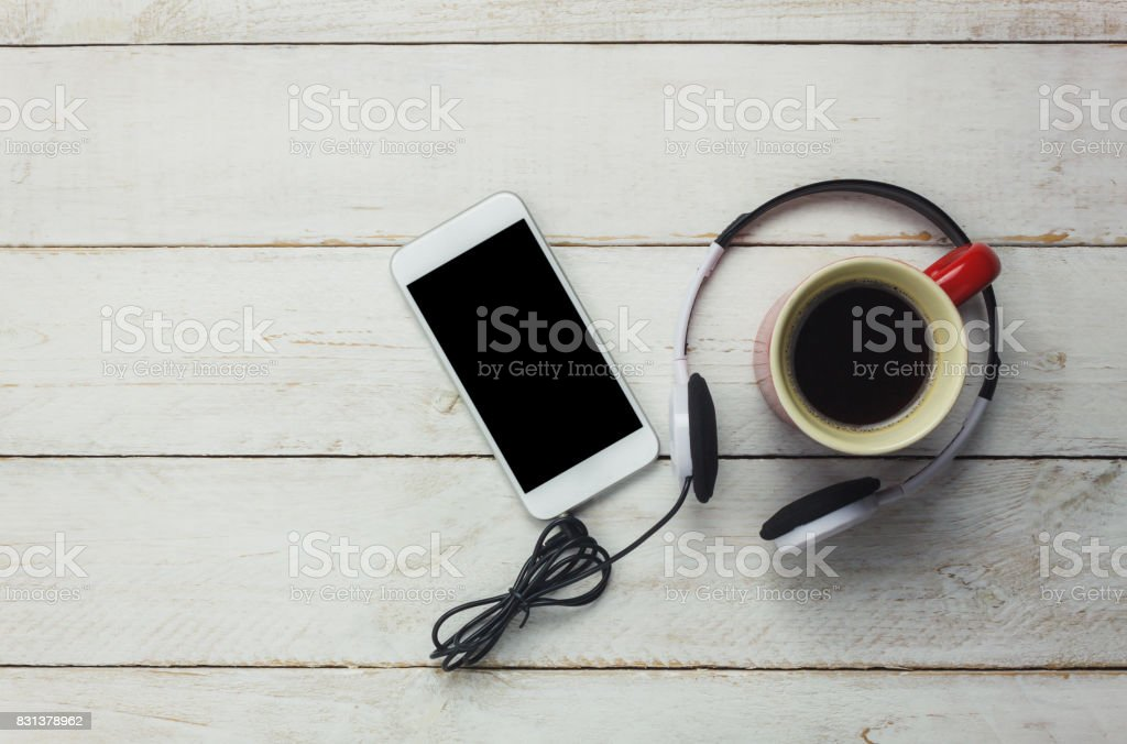 Table top of the technology and music background concept.Mix object and coffee drink on modern rustic white wooden background. Empty space for free text or word creative design. Overhead view. stock photo