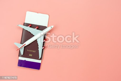 istock Table top view accessory of accessory travel in holiday background concept.Flat lay of airplane with passport and boarding pass ticket on modern rustic pink paper at home studio office desk.copy space 1167627470
