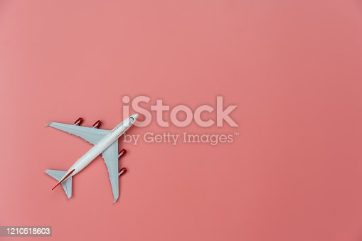 624266324 istock photo Table top view accessory of accessory travel in holiday background concept.Flat lay of white airplane on modern rustic pink paper at home studio office desk.copy space for creative design text. 1210518603