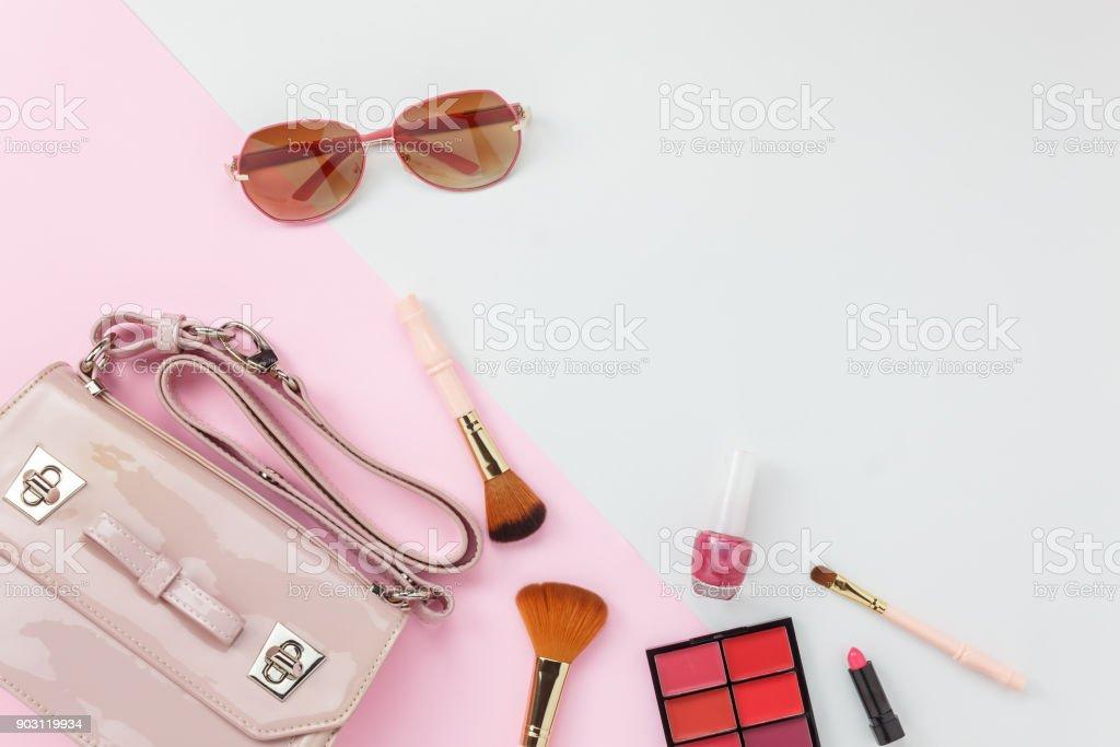 Accessoire de vue de dessus de table de vêtements femmes prévoient de voyager dans le concept de contexte de vacances. Sac à main avec de nombreux articles essentiels lunettes cosmétiques et soleil sur moderne papier blanc & rose. Duo avec ton pastel. - Photo