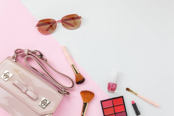 table top view accessory of clothing women  plan to travel in holiday background concept.hand bag with many essential  items cosmetic and sun glasses on modern white & pink paper.duo with pastel tone. - acessório imagens e fotografias de stock