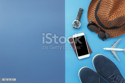 istock Table top view accessory of clothing women  plan to travel in holiday background concept.Mobile phone with many essential  items hat & shoes on modern rustic duo blue paper with space creative design. 921976108