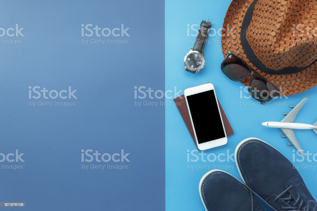 Table top view accessory of clothing women  plan to travel in holiday background concept.Mobile phone with many essential  items hat & shoes on modern rustic duo blue paper with space creative design. stock photo